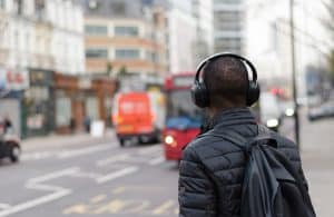 A man in headphones stands on the side of a city street.