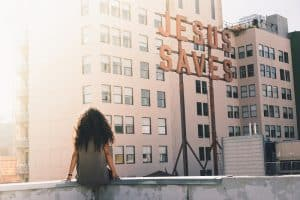 """A sits in front of a building which displays a sign reading """"Jesus Saves."""""""