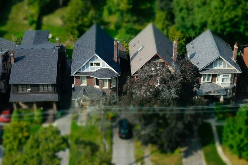 Aerial view of houses with trees around them.