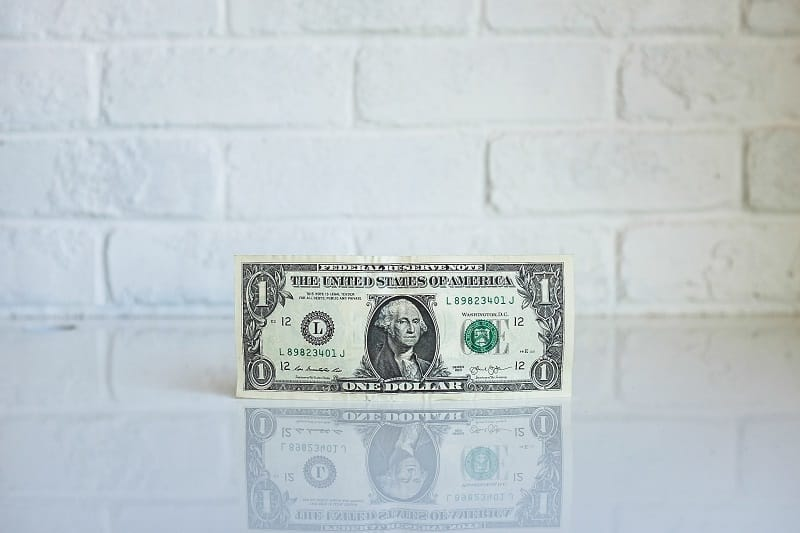 Dollar bill leaning against white wall on shiny white surface.