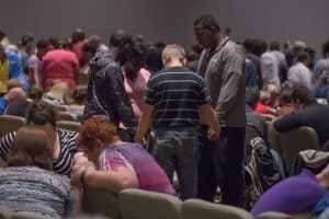 Group of people praying together.