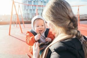 Mom with blonde hair holds infant son at a playground.