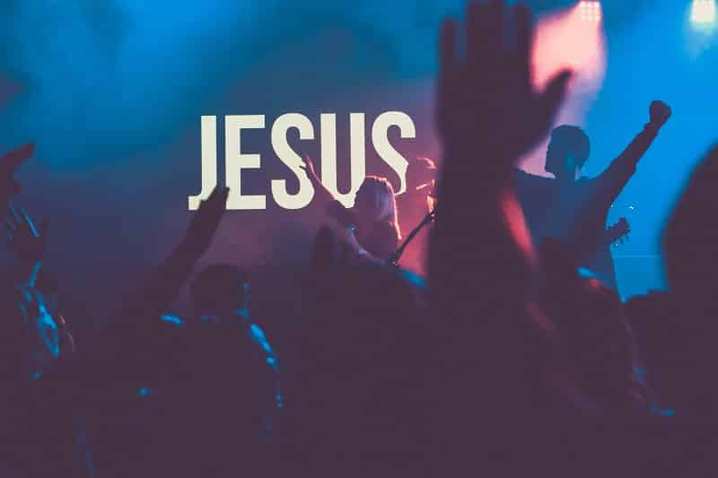 """Low lit room with hands lifted in worship. Screen says """"JESUS."""""""