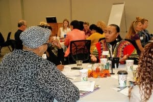 Attendees discussing around a table at a Caring For Kids roundtable meeting.