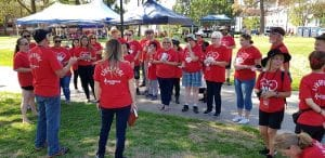 Group in matching red shirts gather to organize event.