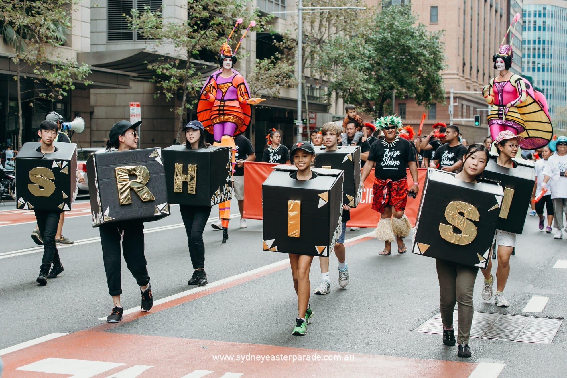 Young people walking through the city wearing colorful boxes with letters in a parade.
