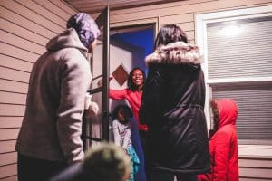 Family knocks on door of woman with her son.