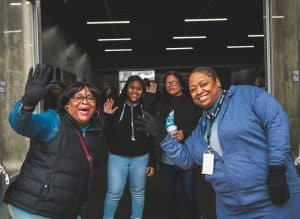 4 smiling African American women wave and welcome people to a church gathering in Omaha.