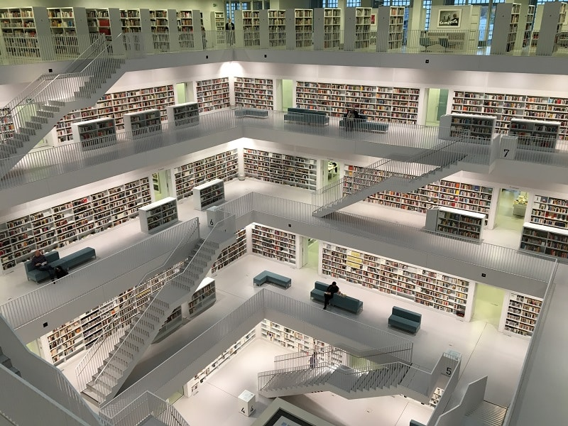 Aerial shot of massive library with white floors and staircases.