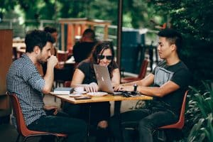 Group of three young people meeting at a coffee shop outside.