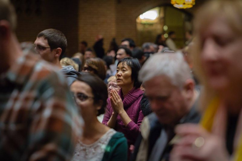 Asian woman in crowd of praying people.