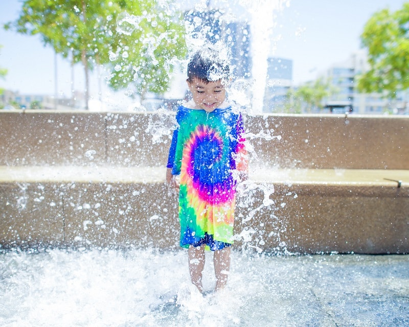 Asian boy in tiedye shirt plays in fountain.