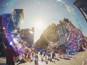 Parade of people walking through city. Bubbles.