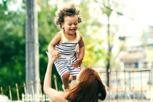 Mom with red hair tosses smiling child with curly brown hair in the air.