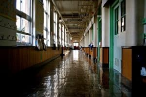 Empty school hallway with bookbags hung on walls.
