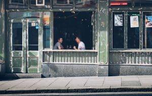 Two men sit in a restaurant window talking over drinks.