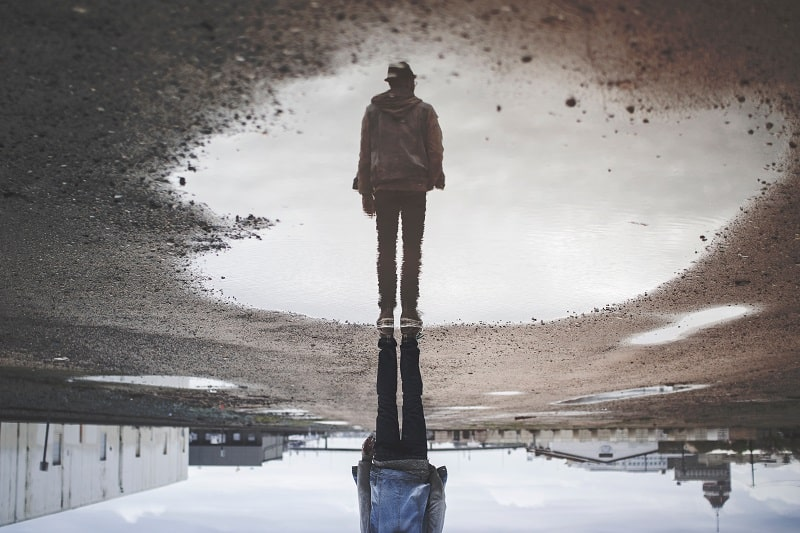 Man stands and his reflection shows off puddle on gray day.