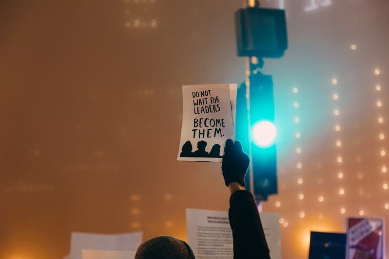 "Man holds sign that says, ""Do not wait for leaders. Become them."""