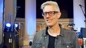 Matt Maher smiles at camera with microphones and stage in background.