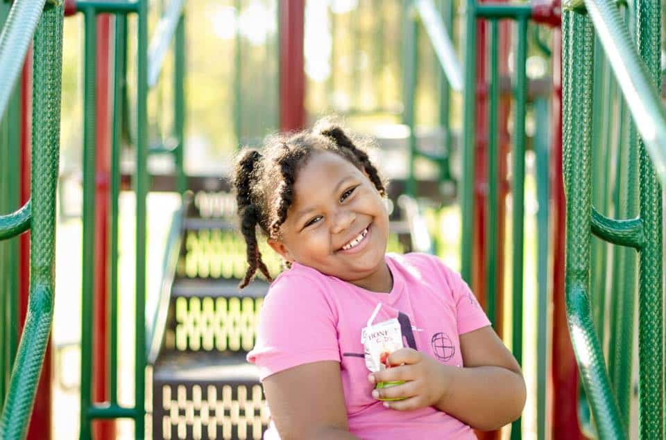 Girl smiling on playground wearing pink shirt.