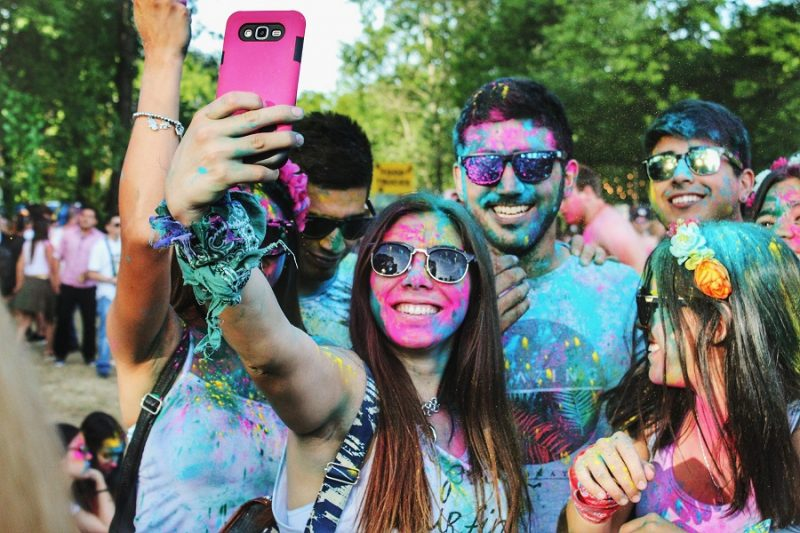 Group of young adults covered in powder paint taking selfie.