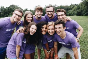 Group of teens in purple #HowtoLife shirts smile